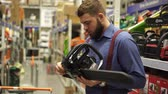 comparar : A man in a hardware store chooses a chainsaw.