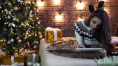 sweater : A young woman with a tablet in the atmosphere of Christmas and New year. Stockvideo