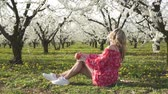 çiçekli : Spring, flowering trees, a young woman eating an apple in a fruit garden. Stok Video