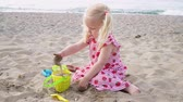 balde : Child girl blonde plays on the sandy beach of the sea. Vídeos