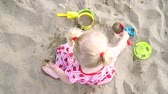 balde : Baby girl playing in the sand with a spatula and a bucket.