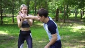 verdediging : Beautiful woman studying martial arts with an instructor. Stockvideo