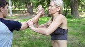 verdediging : Woman trains in martial arts techniques in the park. A woman goes in for sports.