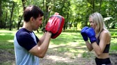 rękawice bokserskie : A woman in boxing gloves is training with a boxing trainer.