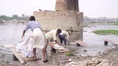 werkkleding : Agra, India, - March 2020. Men wash clothes on a river in India. Stockvideo