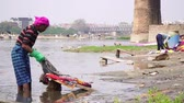 honesto : Agra, India, - March 2020. Indian worker washing clothes on the river.