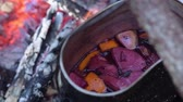 konvice : Mulled wine in a pot over a campfire hike.