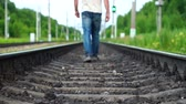 Man walking away along railway track Stock Footage