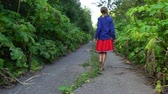 bozót : Teen girl goes along abandoned road overgrown by hogweed