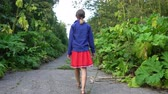 Girl goes along abandoned road overgrown by hogweed Stock Footage