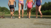 Happy children running and jumping in water from a pier Stock Footage