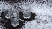 Empty glasses of vodka standing on the wooden table covered with snow Stok Video