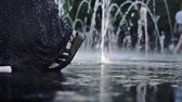 junção : Female feet standing between sprays of floor fontain in a summer evening