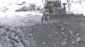 enrichment : The bulldozer works in a career in the winter. Tractor with a scoop on the work site of a quarry of minerals. Stock Footage