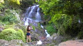 Travel and technology. Young woman in sportswear taking photo of big waterfall on her smartphone.