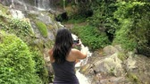 Girl Take a Picture of a Waterfall on a Mobile Phone Stok Video
