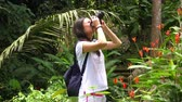 Holidays and Tourism concept - beautiful Woman Taking Picture in the Jungle Stok Video