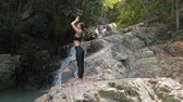 Young Woman Meditates at the Waterfall