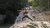 Asian Woman Practicing Yoga at the Waterfall Stok Video