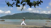 Woman Practicing Yoga at the Sea on Tropical Island Stok Video