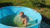 fürdőkád : Slow motion shot of little boy aged one year is bathed in artificial baby pool on hot summer day Stock mozgókép