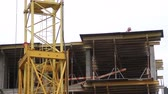 manmetro : Construction. Man walks on the top of building. Crane. Stock Footage