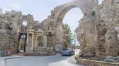manavgat : The main city road - Liman Cadessi runs through the Monumental Gate, preserved since the times of Romans, nowadays transport rides through this ancient stone arch, Side, Turkey. Stock Footage