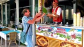 porta : ANTALYA, TURKEY - MAY 13, 2017: The vendor of traditional Turkish ice cream (dondurma) jokes with client, showing some fun hand tricks with the long stick and ice cream cone, on May 13 in Antalya. Vídeos