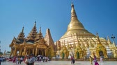 dagon : YANGON, MYANMAR - FEBRUARY 27, 2018: The tourists and Buddhist pilgrims walk around the great Swedagon Pagoda, surrounded by multiple smaller stupas and picturesque pavilions, on February 27 in Yangon