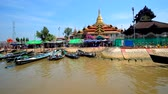 inlay : INLE LAKE, MYANMAR - FEBRUARY 18, 2018: The tourists and pilgrims canoes at wharf of Hpaung Daw U Pagoda in Ywama village, on February 18 in Inle lake.
