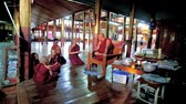 inlay : INLE LAKE, MYANMAR - FEBRUARY 18, 2018: Young boys - samaneras (novice monks) have conversation and drink juice with their mentor bhikkhu in Nga Phe Kyaung Monastery, on February 18 in Inle Lake.