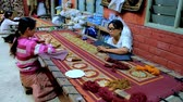 rendilhado : MANDALAY, MYANMAR - FEBRUARY 21, 2018: The Shwe-gui-do Quarter is famous for the workshops, producing embroidered tapestries, decorated with gold, spangles and pearls, on February 21 in Mandalay.