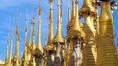 spirál : The row of golden hti decorative umbrellas with bells and wind vanes on the top of small stupas, located in site of Inn Thein Buddha image Shrine, Indein (Inn Thein) village, Inle Lake, Myanmar.