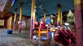inlay : INLE LAKE, MYANMAR - FEBRUARY 18, 2018: The bhikkhu (monk) talks to the boys - samaneras (novice monks) and gives them red robes, Nga Phe Kyaung Monastery of jumping cats, on February 18 in Inle lake