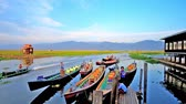 inlay : INLE LAKE, MYANMAR - FEBRUARY 18, 2018: The wharf of Nga Phe Kyaung Monastery of jumping cats with moored canoes, waiting for the tourists, on February 18 in Inle lake
