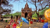slunečník : BAGAN, MYANMAR - FEBRUARY 24, 2018: Traditional colored umbrellas and beautiful dolls are hanging on the tree next to the ancient Buddhist Shrine in archaeological site, on February 24 in Bagan.