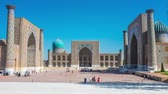 rendilhado : SAMARKAND, UZBEKISTAN – MAY 2, 2015: Visitors enjoy ensemble of the Registan Square with its landmarks: Ulugh Beg Madrasah, the Tilya-Kori Madrasah and the Sher-Dor Madrasah, on May 2 in Samarkand.