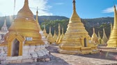 guarda chuva : Walk among the carved golden stupas of Nget Pyaw Taw Paya (Pagoda), located at the mountain foot, next to the entrance to Shwe Oo Min Natural Cave, Pindaya, Myanmar. Vídeos