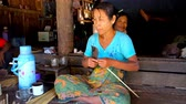 splitting : CHAUNG THA, MYANMAR - MARCH 1, 2018: Burmese woman makes the narrow strips of bamboo for weaving of different stuff - conical hats, plates, baskets, wall or roof panels, on March 1 in Chaung Tha. Stock Footage