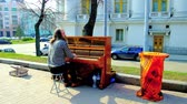 tehetség : KIEV, UKRAINE - APRIL 13, 2018: The street musician entertains people in park on Saint Vladimirs Hill, playing piano, on April 13 in Kiev. Stock mozgókép