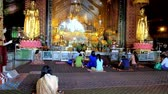 dagon : YANGON, MYANMAR - FEBRUARY 27, 2018: Interior of the prayer hall of Zayer Yar Aung Myay Monastery, people pray at golden altar with many statues of Lord Buddha, on February 27 in Yangon.