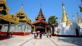 dagon : YANGON, MYANMAR - FEBRUARY 27, 2018: Pilgrims go to the North Gate of Shwedagon Pagoda, surrounded by numerous golden Stupas and Image Houses, on February 27 in Yangon. Stock Footage
