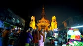 vasi : YANGON, MYANMAR - FEBRUARY 27, 2018: The brightly illuminated Eastern Gate of Swedagon Pagoda with crowded market street on the foreground, on February 27 in Yangon. Stok Video
