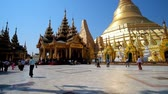 dagon : YANGON, MYANMAR - FEBRUARY 27, 2018: The great architectural ensemble of Shwedagon Pagoda with giant golden stupa and masterpiece image house, located at the East Gate, on February 27 in Yangon Stock Footage