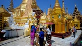dagon : YANGON, MYANMAR - FEBRUARY 27, 2018: The Buddhist devotees perform the ritual of Buddha statue bathing in Shwedagon Pagoda with great golden stupas on background, on February 27 in Yangon Stock Footage