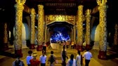 dagon : YANGON, MYANMAR - FEBRUARY 27, 2018:  The covered gallery of the Shwedagon Pagoda East Gate with rich golden ornaments, carved wooden decors, paintings and numerous visitors, on February 27 in Yangon