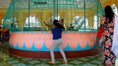 délkelet Ázsia : BAGO, MYANMAR - FEBRUARY 15, 2018: Kids throw coins to pavilion for donations with spinning installation in Shwemawdaw Pagoda, on February 15 in Bago.