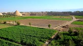 tarihi : Panorama of farm lands, surrounded by medieval adobe rampart of Ghaleh Jalali citadel with a view on preserved yakhchals - ancient evaporative coolers, shaped as pyramids, Kashan, Iran.