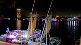 nílus : CAIRO, EGYPT - DECEMBER 23, 2017: The evening walk along the Corniche embankment with a view on feluccas and yachts in tourist port and bright city lights, reflected in Nile, on December 23 in Cairo
