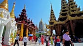 dagon : YANGON, MYANMAR - FEBRUARY 27, 2018: Tourists and pilgrims visit Shwedagon Pagoda, famous for its outstanding architecture, numerous religious objects and places of interest, on February 27 in Yangon.